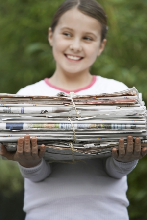 everyday scenes: Pre-teen Girl Recycling Newspapers