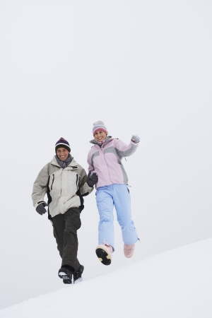Couple in Winter Landscape Running Downhill Stock Photo - 19465755