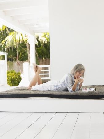 verandah: Woman lying down on day bed on verandah