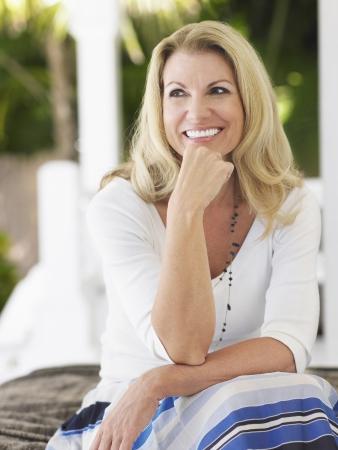 one mature woman only: Woman sitting on verandah portrait LANG_EVOIMAGES