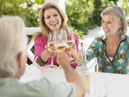 verandah: Three people toasting with wine glasses sitting at verandah table LANG_EVOIMAGES
