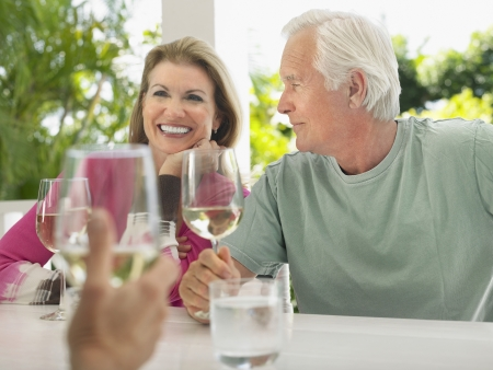 two people with others: Three people sitting at verandah holding wine glasses LANG_EVOIMAGES