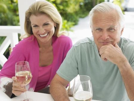 verandah: Couple holding wine glasses sitting at verandah table elevated view LANG_EVOIMAGES