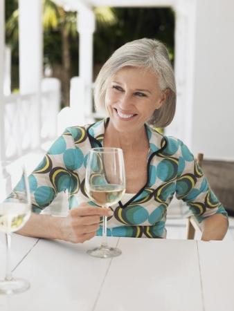 verandah: Woman holding glass of wine at verandah table portrait LANG_EVOIMAGES