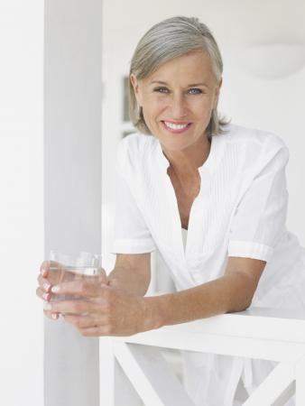 Woman holding glass of water leaning on verandah balustrade portrait Stock Photo