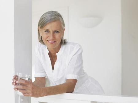 verandah: Woman holding glass of water leaning on verandah balustrade portrait LANG_EVOIMAGES