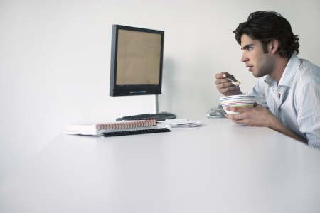 Business man eating sitting at office desk side view Stock Photo - 19465773