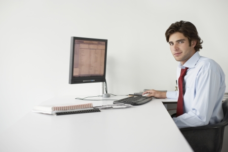 Business man using computer sitting at office desk side view portrait Stock Photo - 19522264