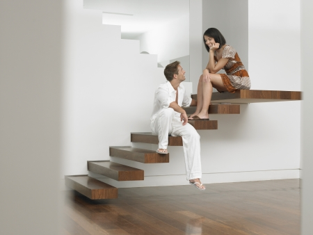 racially diverse: Young Couple Sitting on Stairs LANG_EVOIMAGES
