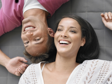 racially diverse: Cheerful Young Couple Lying Down