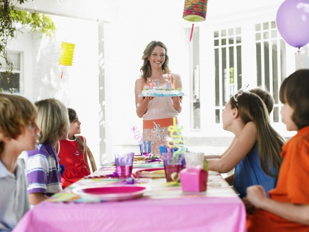 preteen girl: Mother serving cake to children (7-12) at birthday party LANG_EVOIMAGES