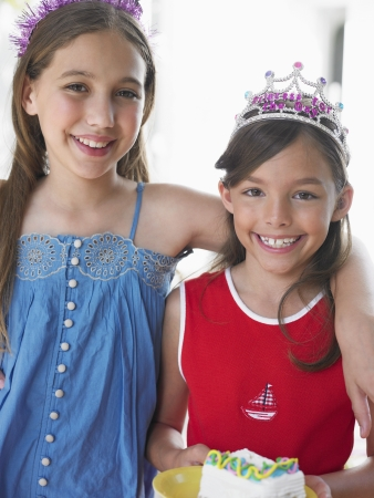 preteen girl: Portrait of two girls (7-9 10-12) in tiaras smiling LANG_EVOIMAGES