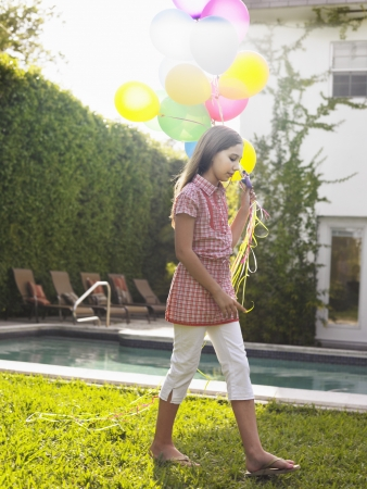 preteen girl: Girl (10-12) walking with balloons by swimming pool