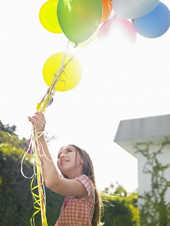 only one girl: Girl holding bunch of balloons looking up smilig