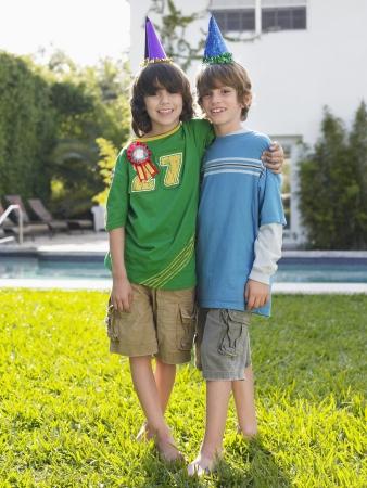 pool preteen: Portrait of two boys (10-12) in party hats in yard