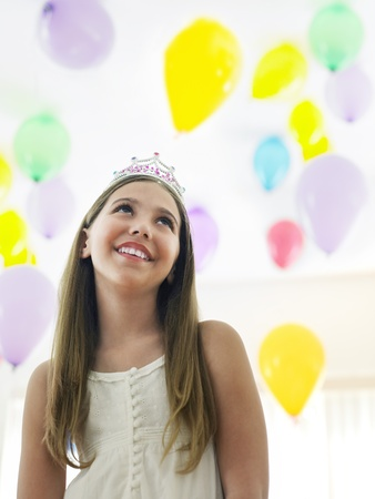 preteen girl: Girl (10-12) in tiara smiling looking up at balloons