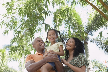 two women and one man: Parents with daughter (5-6 years) in tropical forest low angle view portrait LANG_EVOIMAGES