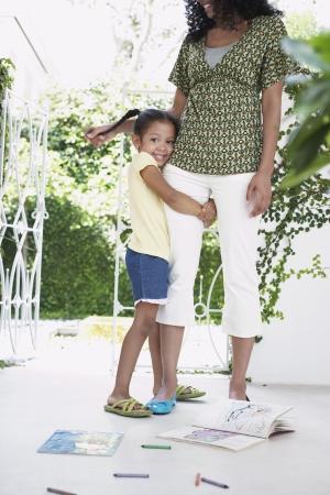 verandah: Girl (5-6 years) hugging mothers leg standing on verandah LANG_EVOIMAGES