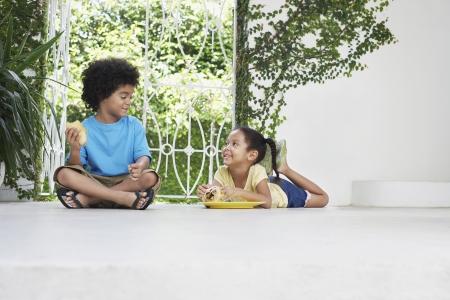 verandah: Boy and girl (5-6 years) eating on verandah floor LANG_EVOIMAGES