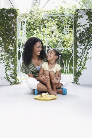 verandah: Mother and daughter (5-6 years) sitting on verandah floor