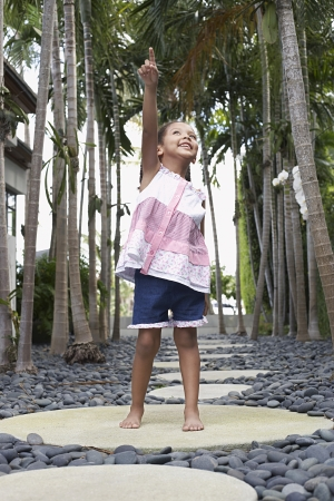 stepping stone: Girl (5-6 years) standing on stepping stone on path pointing up