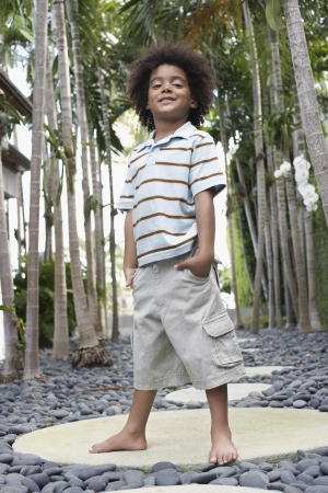stepping stone: Boy (5-6 years) standing on stepping stone on path portrait low angle view LANG_EVOIMAGES