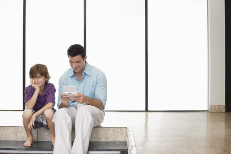role reversal: Father and son (7-9) sitting on floor indoors man playing handheld game