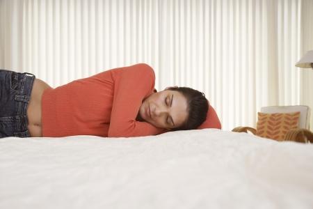 Mid-adult woman sleeping on bed Stock Photo