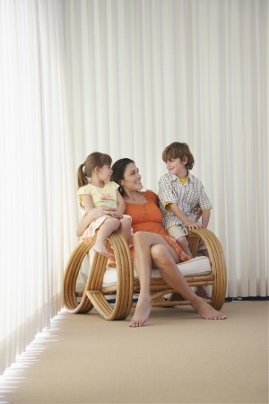 Mother with son (7-9) and daughter (5-6) sitting in armchair Stock Photo - 19522511