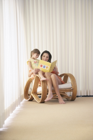 legs crossed at knee: Mother and daughter (5-6) sitting in armchair reading book