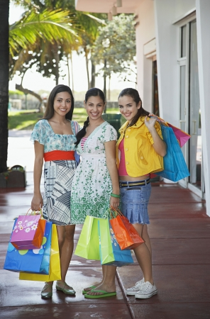 Three teenage girls (16-17) carrying shopping bags standing on street portrait Stock Photo - 19546526
