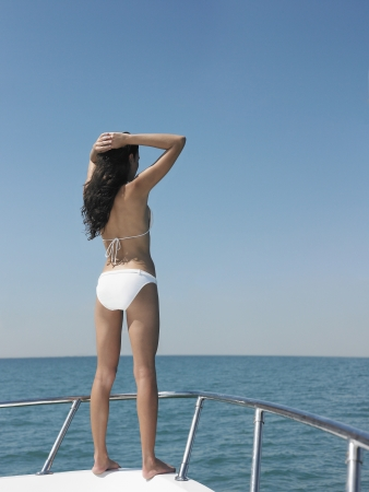 Young woman in bikini standing on bow of yacht looking at sea back view Stock Photo - 19522590
