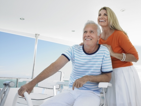 sailing yacht: Smiling middle-aged couple at helm of yacht