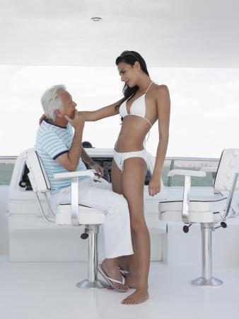 timon barco: Hombre de mediana edad y una mujer joven en el tim�n de la vista lateral de yates