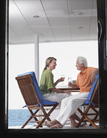 view through door: Middle-aged couple drinking wine on yacht profile view through door