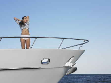 adult cruise: Young woman standing in bow of yacht