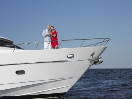 motorboat: Middle-aged couple standing in bow of yacht