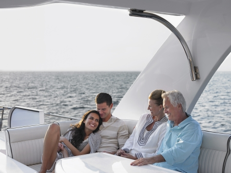 boat deck: Young and middle-aged couple relaxing on yacht