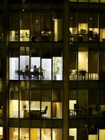 mixed age range: Business meeting viewed through illuminated window of office block at night