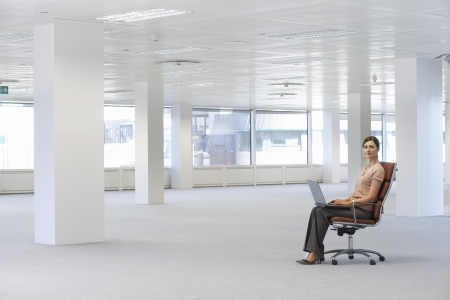business roles: Woman Using Laptop in Empty Office Space