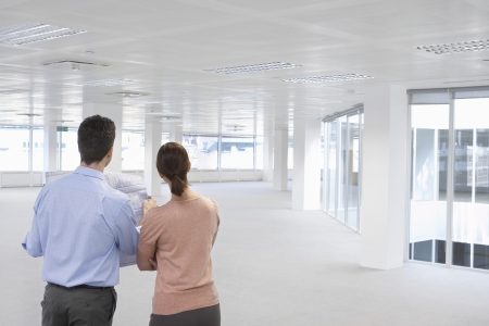 Businesspeople with Blueprints in Empty Office Stock Photo