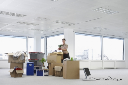 relocating: Businesswoman in Office with Moving Supplies