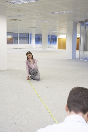 new office space: Man and Woman Measuring New Office Space