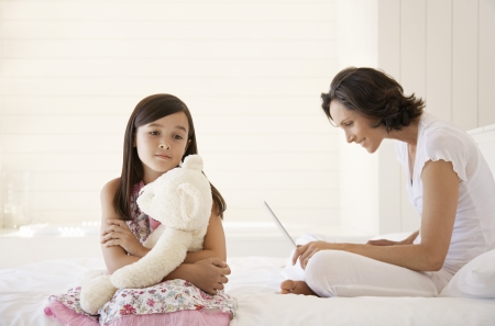 browses: Little Girl Holding a Teddy Bear While Her Mother Browses the Web