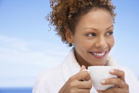 mujer tomando cafe: Mujer joven que tiene café de la mañana LANG_EVOIMAGES