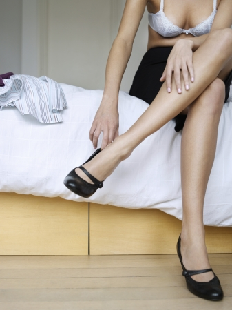low section: Young woman sitting on bed getting dressed low section LANG_EVOIMAGES