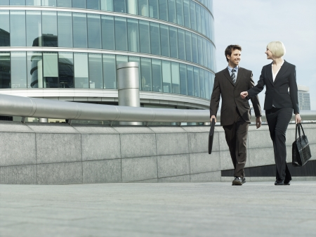 Business man and woman walking outside office building talking and smiling