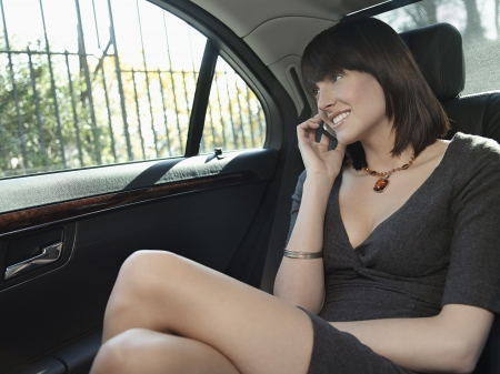 legs crossed at knee: Mid adult woman at back seat of car using mobile phone
