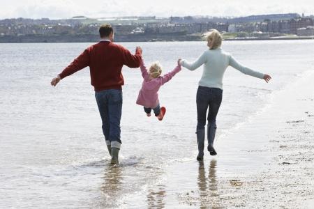 lifting hands: Parents lifting daughter (5-6) at ocean