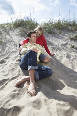 mid afternoon: Couple sitting on beach embracing